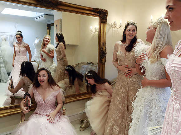 Debutantes Maria Austin, Amelia Simmons, Sophie Bonello, Zoe Rawson, and Georgina Riddle attend a dress-fitting for Queen Charlotte's Ball in central London, United Kingdom.