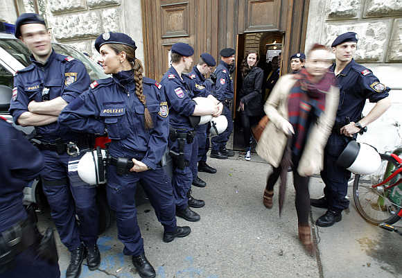 Police are seen as students leave Vienna University through a side entrance in Vienna, Austria.