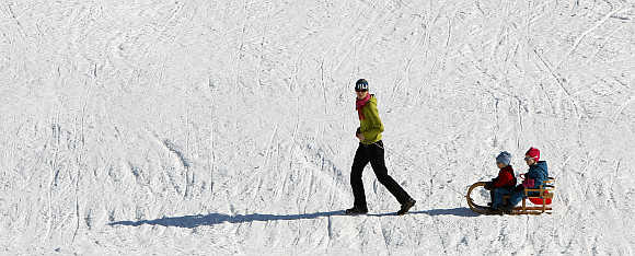 A woman pulls children on a sledge during a sunny winter weather in Oberstdorf, Germany.
