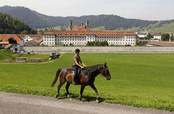 A woman rides a horse in front of Kloster Einsiedeln abbey in the central Swiss town of Einsiedeln.