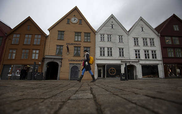 A woman walks near Bryggen (the Wharf) near the marina in downtown Bergen, Norway.