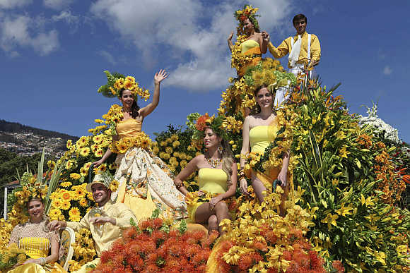 People participate in a parade on a float at the Madeira Island Flowers Festival in Funchal, Portugal.