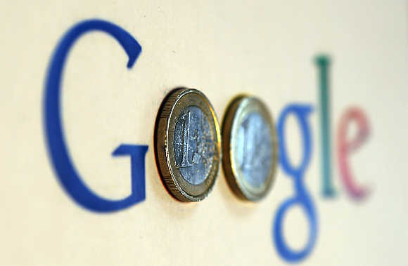 An illustration picture shows a Google logo with two one Euro coins, taken in Munich, Germany.