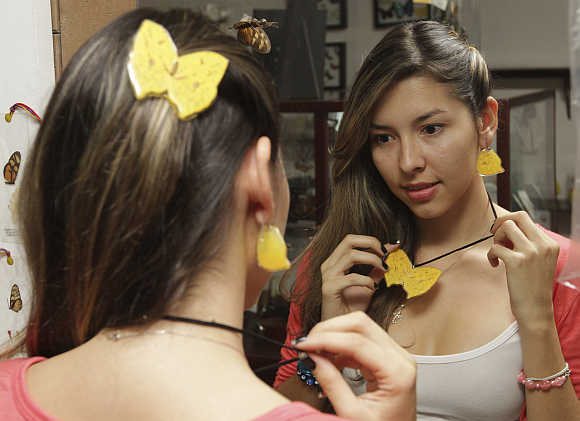 A woman tries on accessories made of butterflies that died naturally in a hatchery in Cali, Colombia.
