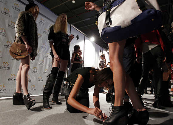 A model has her toe nails painted backstage at a fashion show in Buenos Aires.