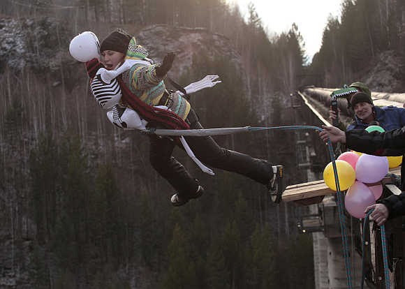A woman, dressed in a Halloween costume, takes a rope jump from a 144 feet high water pipe bridge in the Siberian Taiga area outside Krasnoyarsk, Russia.