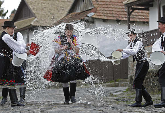 A woman runs as men throw water at her as part of traditional Easter celebrations near Budapest.