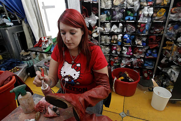 A woman mends shoes backstage before Cirque du Soleil's show in Lima.