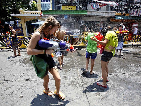 Tourists use toy guns as they participate in a water fight during the Songkran Festival celebration at Khaosan road in Bangkok.