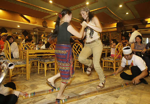 A waitress teaches a tourist how to dance the 'Tinikling', a native bamboo dance in a Manila restaurant.