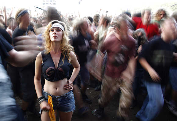 A reveller listens to music as other dance in Kostrzyn-upon-Odra River, close to the Polish and German border, in Poland.
