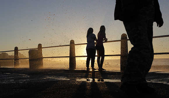 People cool off as waves hit the sea point promenade in Cape Town.