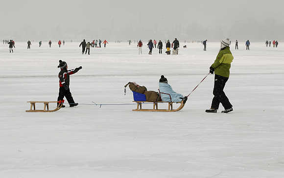 A woman pulls two sleds on the frozen Lake Pf