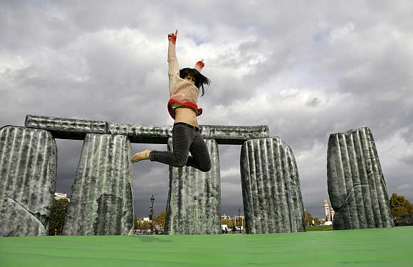A woman jumps on 'Sacrilege, 2012' art works by Jeremy Deller at the Esplande des Invalides in Paris, France.