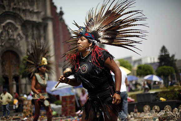 A group performs an Aztec dance for tourists outside the Metropolitan Cathedral in Mexico City.