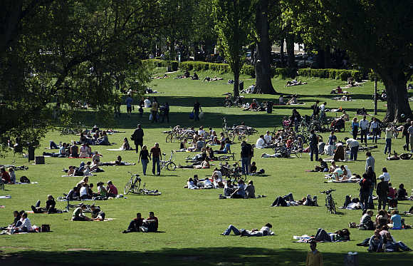 People enjoy the sunny weather in a park in Heidelberg, 90km south of Frankfurt, Germany.