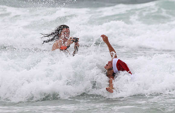 A woman enjoys the waves as her friend takes pictures on a cold and rainy day on Bondi Beach in Sydney, Australia.