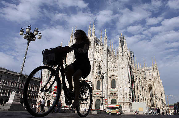 A woman rides a bicycle in front of the Duomo cathedral in downtown Milan, Italy.