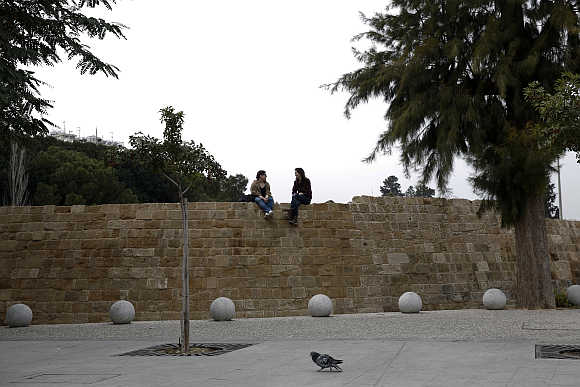 Two girls talk sitting on the Venetian Walls surrounding the old town of capital Nicosia, Cyprus.