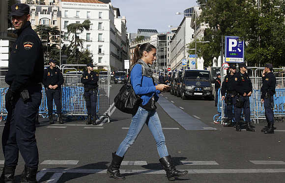 A woman walks past police deployed around Spain's parliament in Madrid.