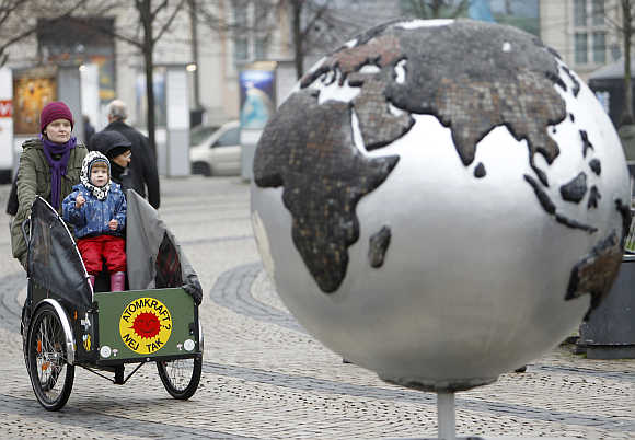 A woman rides a bicycle past a globe in downtown Copenhagen, Denmark.