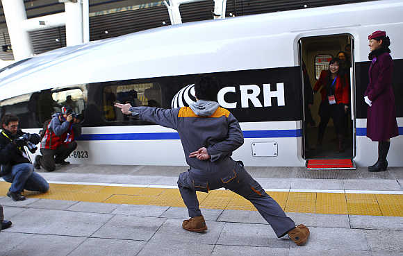 A journalist poses for a photo in front of a high-speed train at Beijing West Railway station, China.