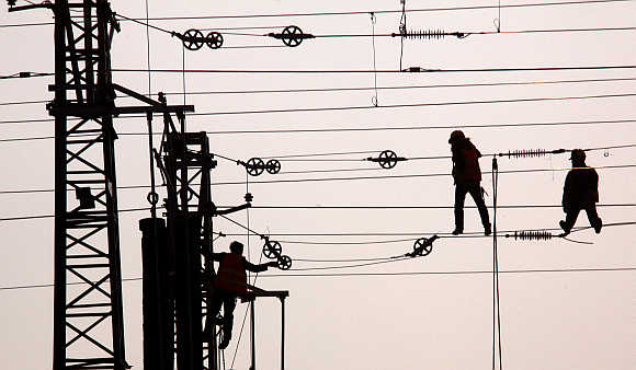 Workmen repair power lines on the outskirts of Beijing, China.
