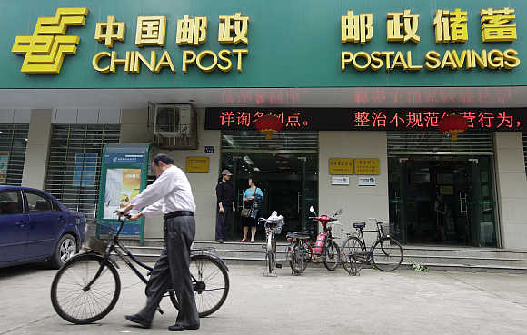 A man pushes his bicycle past a branch of China Post's Postal Savings Bank of China in Wuhan, Hubei province.