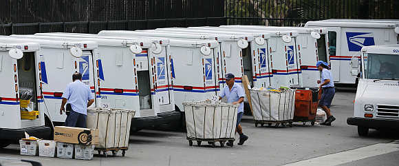 US postal workers load their trucks with mail from their postal station in Carlsbad, California.