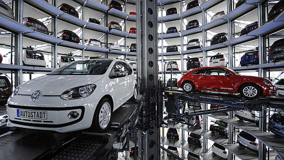 A Volkswagen Beetle, right, and an UP!, left, in a delivery tower at the company's headquarter in Wolfsburg, Germany.