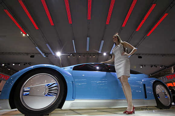 A model poses next to a Toyota Fine S hybrid car in Sao Paulo, Brazil.