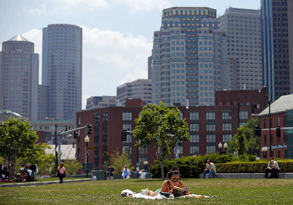 A woman reads a book on the Rose Kennedy Greenway in Boston, Massachusetts, United States.