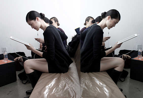 A model is reflected in a mirror while she reads her iPad backstage before a fashion show in New York City.