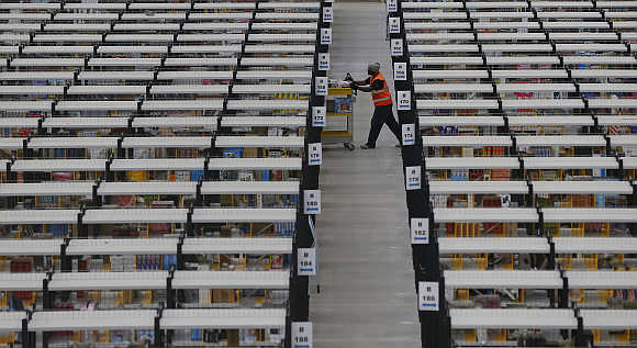 A worker collects orders at Amazon's warehouse in Rugeley, central England.
