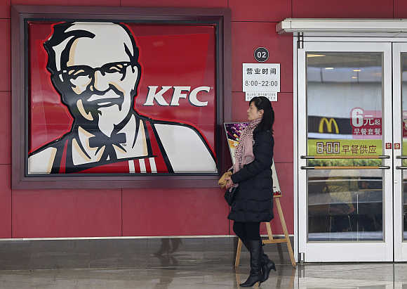 A woman walks past a KFC restaurant in Wuhan, Hubei province, China.