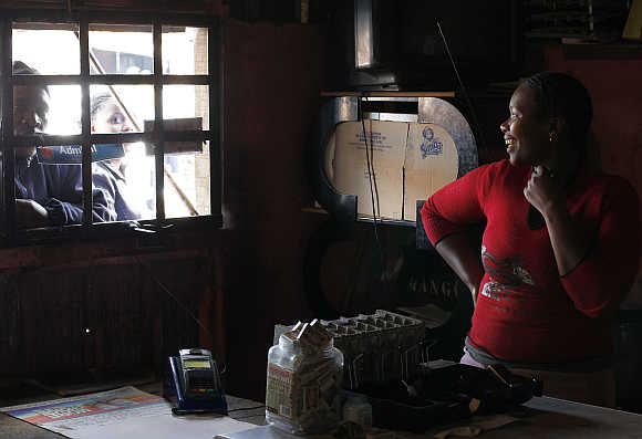 Trader Nono Dawane greets customers at her small shop selling cigarettes and cold drinks in Cape Town's Khayelitsha township, South Africa.