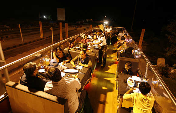People dine on a double-decker bus converted into a mobile restaurant in Ahmedabad.