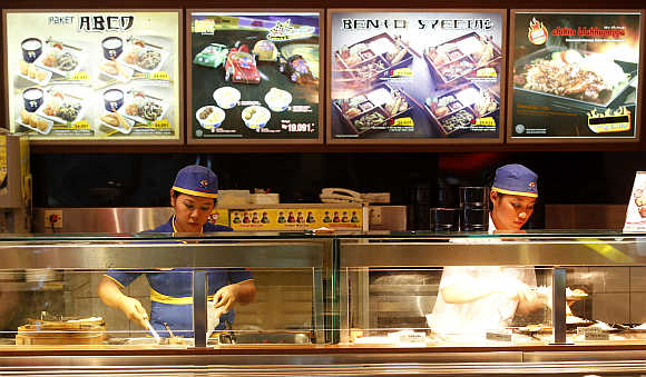 Workers prepare food at a fast food outlet in Jakarta, Indonesia.