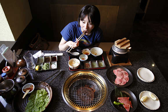 Rina Mitsutake eats a piece of beef strip in Yokohama, south of Tokyo, Japan.