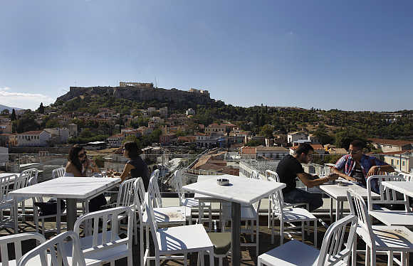People sit in a cafe with the Acropolis hill in the background in central Athens, Greece.