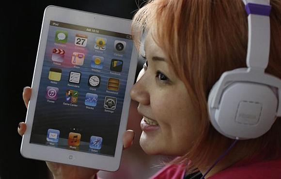 A woman holds a mock model of Apple's new iPad mini as she waits for the release of the tablet.