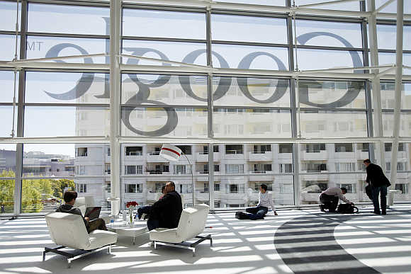 Attendees sit in front of a Google logo at Moscone Center in San Francisco, Califronia.
