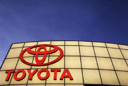 The Toyota logo is lit up above its dealership.