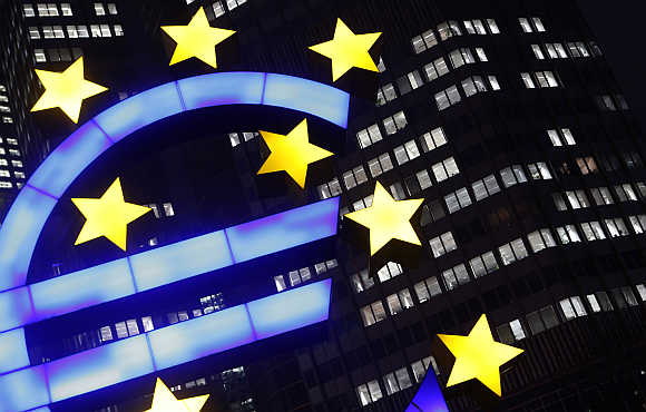 An illuminated euro sign in front of the European Central Bank headquarters in Frankfurt, Germany.