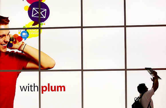 A man uses an iPad to take a video of the Plum Mobile exhibit in New Orleans, Louisiana, United States.