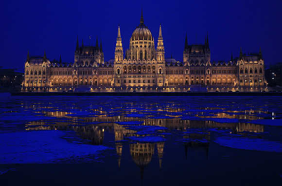 Hungarian Parliament building is reflected on the icy Danube river in Budapest.