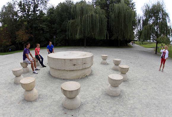 Tourists sit around the Table of Silence, a limestone sculpture, in Targu Jiu, 300km west of Bucharest.