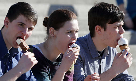 Visitors eat ice cream at the CeBit computer fair in Hanover, Germany.