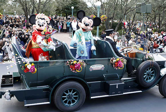 Disney cartoon characters Mickey, right, and Minnie Mouse, left, dressed in kimonos, wave from an open car at Tokyo Disneyland in Urayasu, Japan.