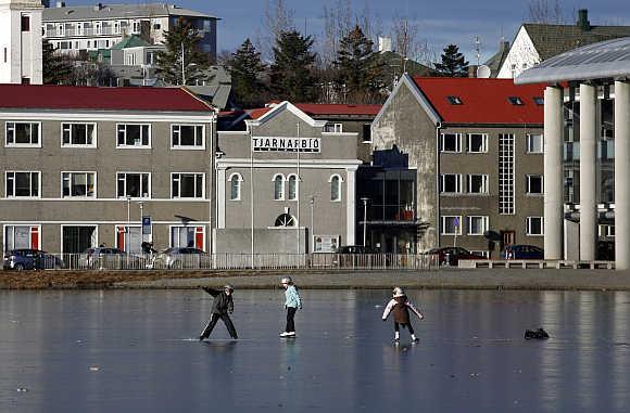 Children skate on the ice of the frozen Tjoernin lake in central Reykjavik, Iceland.